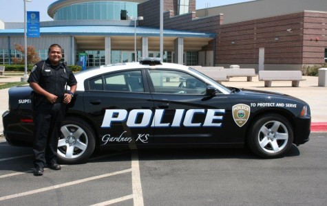 SRO Anthony Garcia poses by his police car.