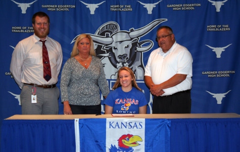 Marissa Gray poses with her track coach John Yockey and her family after signing to the University of Kansas Rowing Team.