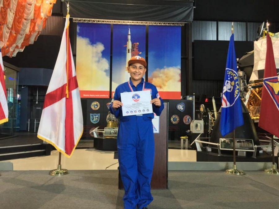 Daniel Villalobos poses in the space academy with his certificate of completion. He was selected to attend this program.