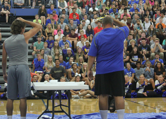 As the audience looks on, senior Hunter Skeens and football coach Marvin Diener smash an egg on top of their heads. The participants played