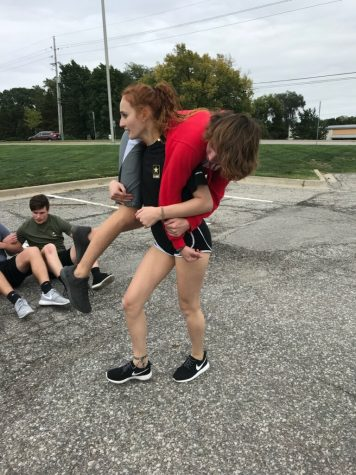 A delayed entry program recruit carries another recruit during a PT session. Photo Courtesy of: SSG Courtney Hess